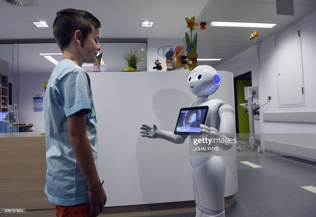A young boy talks with the robot Pepper during a press conference on June 13, 2016 at the CHR Citadel hospital centers of Liege. the CHR Citadel hospital centers of Liege and AZ Damiaan of Ostend will welcome next week a humanoid robot intended to guide and to inform the visitors who appear in their entrance hall. The new robot on which these hospitals decided to buy, conscript Pepper, is more tall(140 cms), more mobile and more adapted to the missions of hospitality. It was adapted to the specific expectations of the healthcare professionals to support the teams ready in the posts of reception. / AFP / JOHN