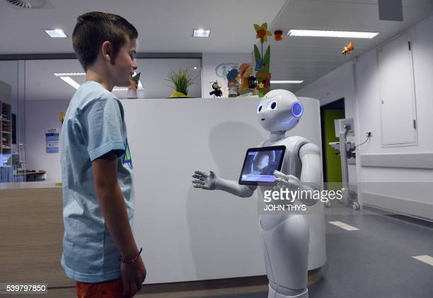 A young boy talks with the robot Pepper during a press conference on June 13 2016 at the CHR Citadel hospital centers of Liege the CHR Citadel...