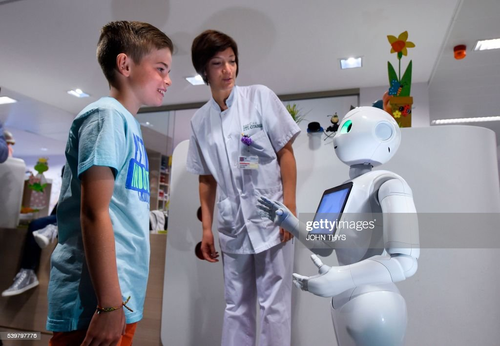A young boy talks with the robot Pepper next to a nurse during a press conference on June 13, 2016 at the CHR Citadel hospital centers of Liege. the CHR Citadel hospital centers of Liege and AZ Damiaan of Ostend will welcome next week a humanoid robot intended to guide and to inform the visitors who appear in their entrance hall. The new robot on which these hospitals decided to buy, conscript Pepper, is more tall(140 cms), more mobile and more adapted to the missions of hospitality. It was adapted to the specific expectations of the healthcare professionals to support the teams ready in the posts of reception. / AFP / JOHN
