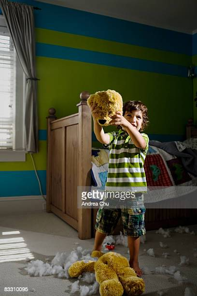 Young boy tearing head of toy bear in bedroom.