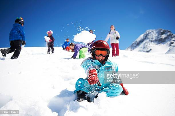 Young boy throwing snowball whilst friends play behind him