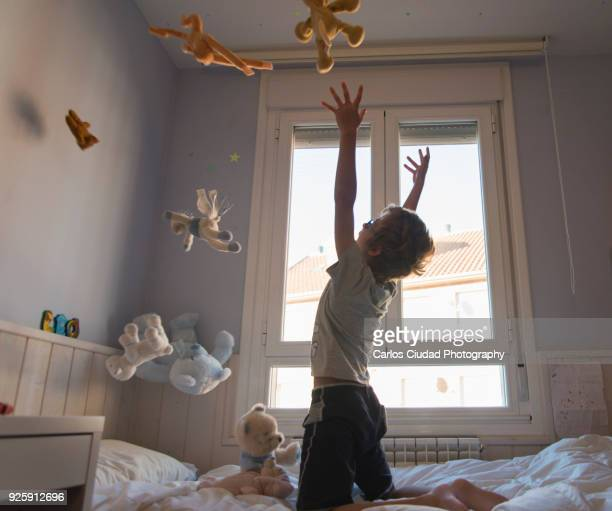 Young boy throwing teddy bears in air