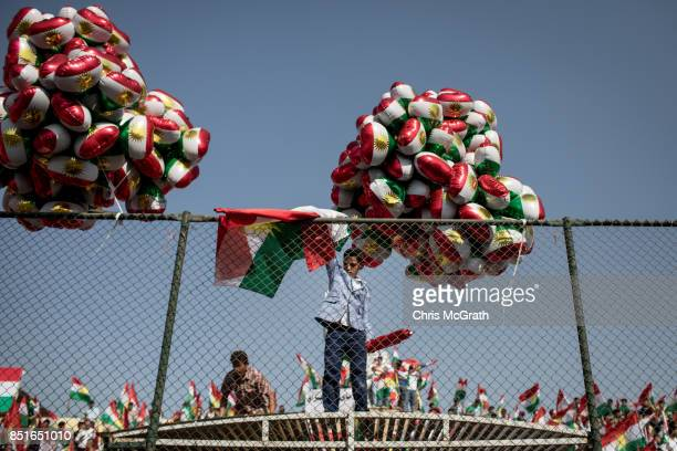 A young boy throws a Kurdish flag over a fence to supporters awaiting the arrival of Kurdish President Masoud Barzani during a rally for the upcoming...