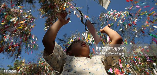 A young boy ties a paper strip with his wish on it onto a bamboo decoration during the Tanabata festival at the Hatamono shrine on July 7 2013 in...