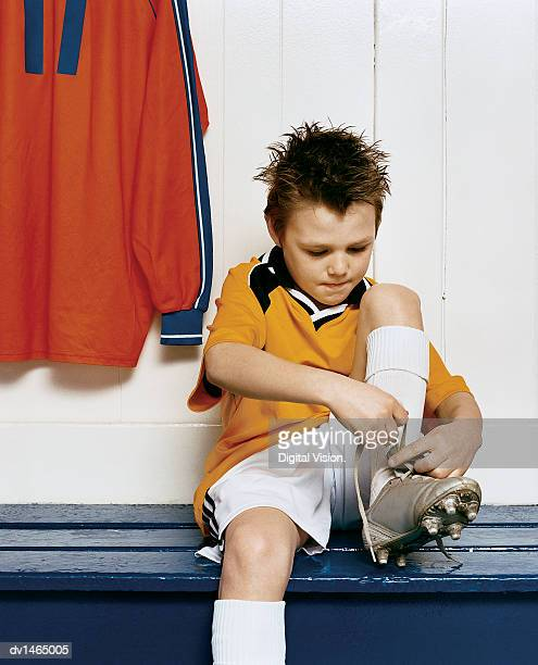 young boy ties the laces of his football boot while sitting on a bench in a changing room - young boys changing in locker room stock pictures, royalty-free photos & images