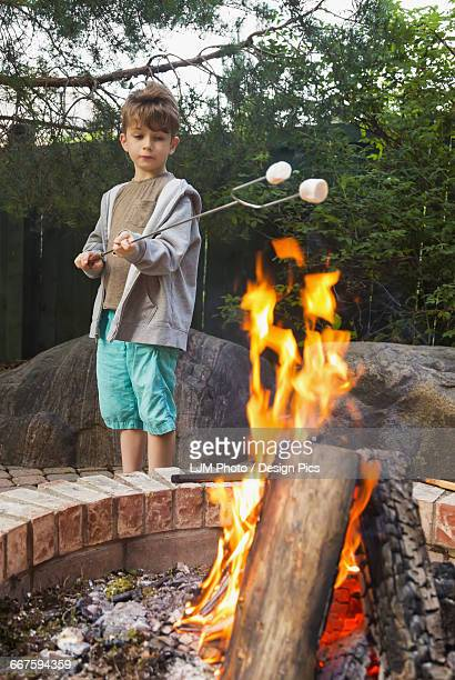 Young boy toasting marshmallows on an open fire in a backyard