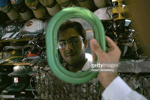 A young boy tries on a pair of glasses in a street shop on August 16 in the North West Frontier Province's capital of Peshawar Pakistan