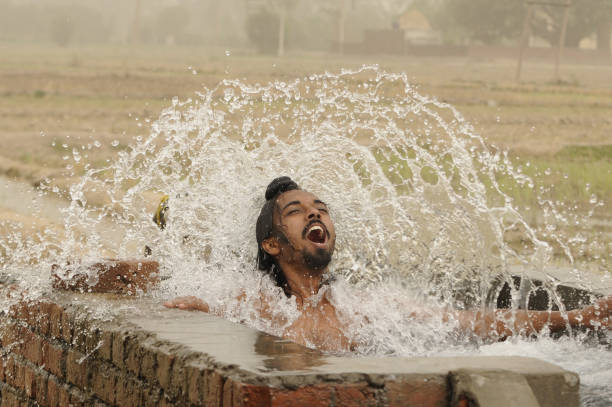 A young boy tries to beat the heat under tube well during the dusty and humid weather on June 14 2018 in Patiala India Many areas in North India saw..