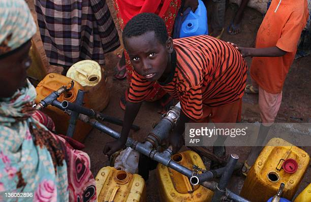A young boy tries to collect water at the Transit Centre in Dolo Ado Ethiopia on December 15 2011 Over 300000 refugees have fled severe drought...