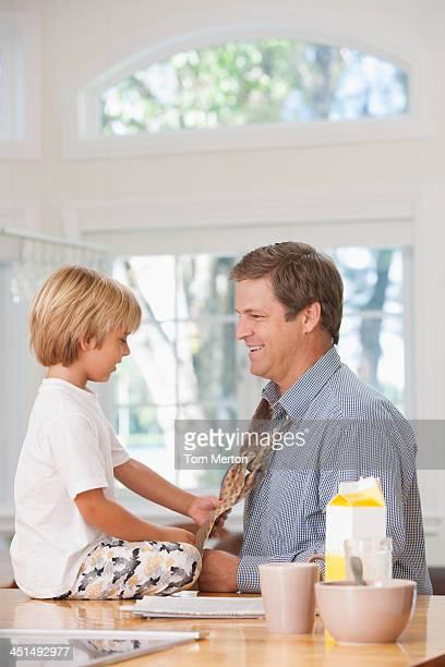 Young boy tying man's necktie in kitchen