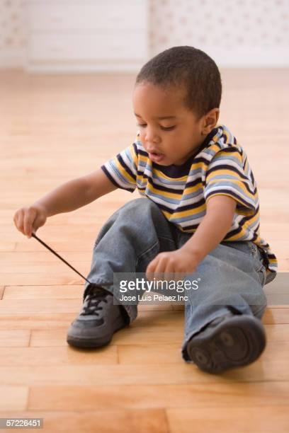 Young boy tying shoe