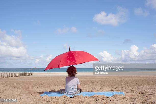 young boy under a parasol - sunshade stock pictures, royalty-free photos & images