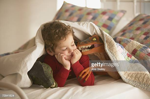young boy under covers in bed with toy dinosaurs - dinosauro foto e immagini stock