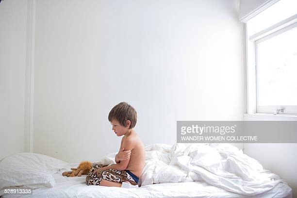 Young boy upset on white bed sheets in room