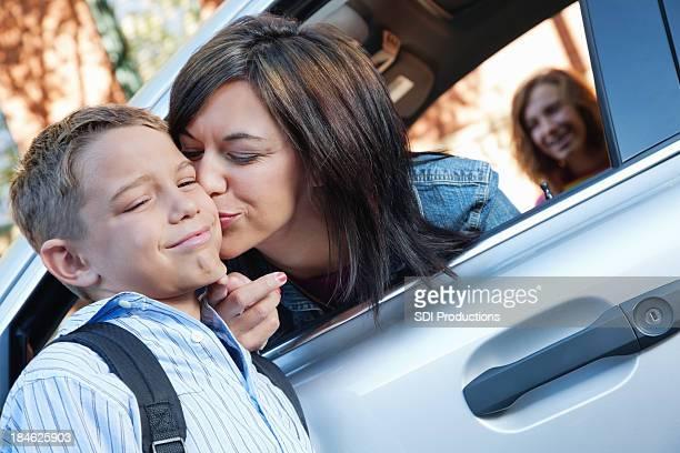 Giovane ragazzo arrabbiato con la mamma addio bacio a scuola