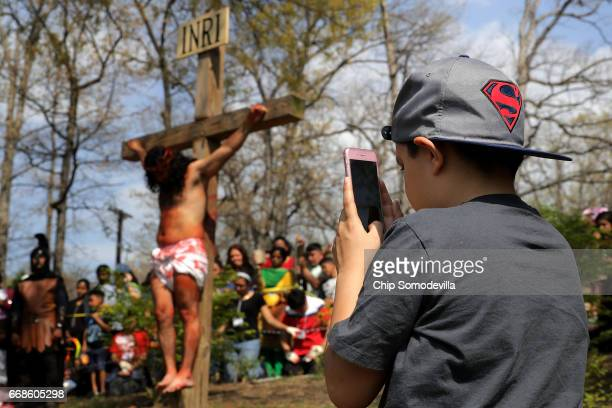 A young boy uses an iPhone to record as Henry Colindres portrays Jesus being crucified during a traditional Via Crucis or Way of the Cross procession...