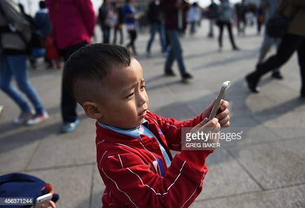 A young boy uses an iPhone to take photos in Tiananmen Square in Beijing on September 30 2014 Apple said on September 30 it will begin selling its...