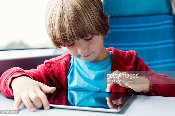 Young boy uses his tablet on the train