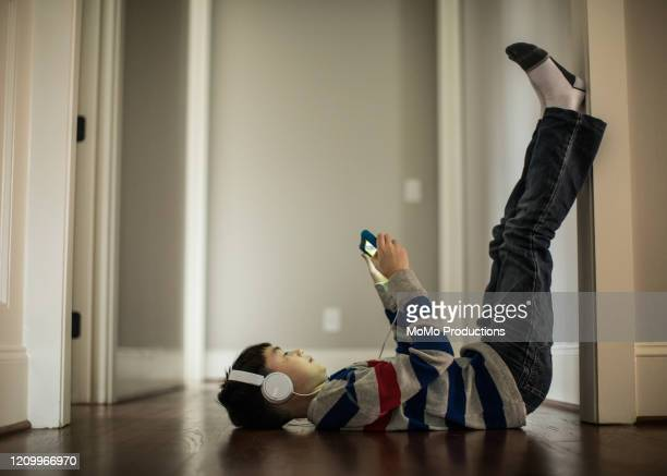 young boy using digital tablet and headphones at home - 男子生徒 ストックフォトと画像