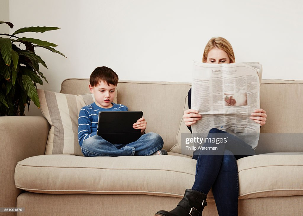Young boy using digital tablet, mother reading newspaper : Stock Photo