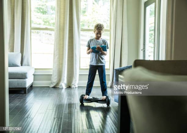 young boy using digital tablet while riding hoverboard - hoverboard stock pictures, royalty-free photos & images