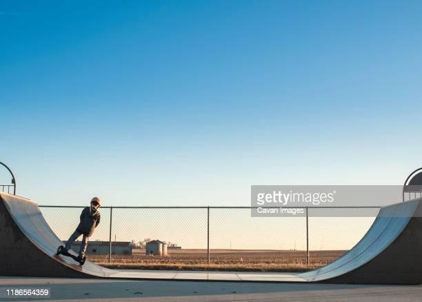 young boy using half pipe ramp at the skate park on sunny day - skateboardpark stockfoto's en -beelden
