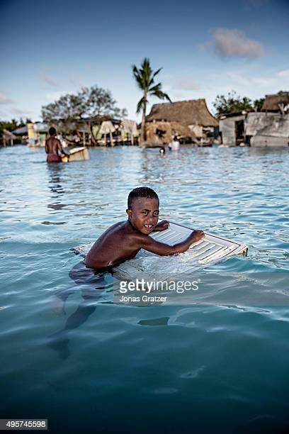 A young boy using rubble to float around the village Eita Large parts of the village drowned in the sea when the tide comes in The people of Kiribati...