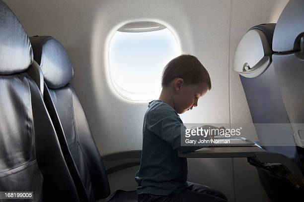 young boy using tablet on aeroplane