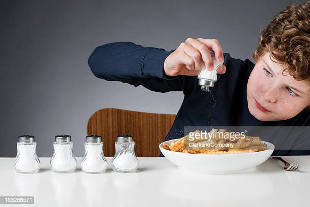 Young Boy Using Too Much Salt