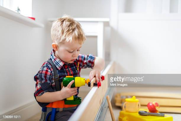 young boy using toy power tool at home - toy stock pictures, royalty-free photos & images