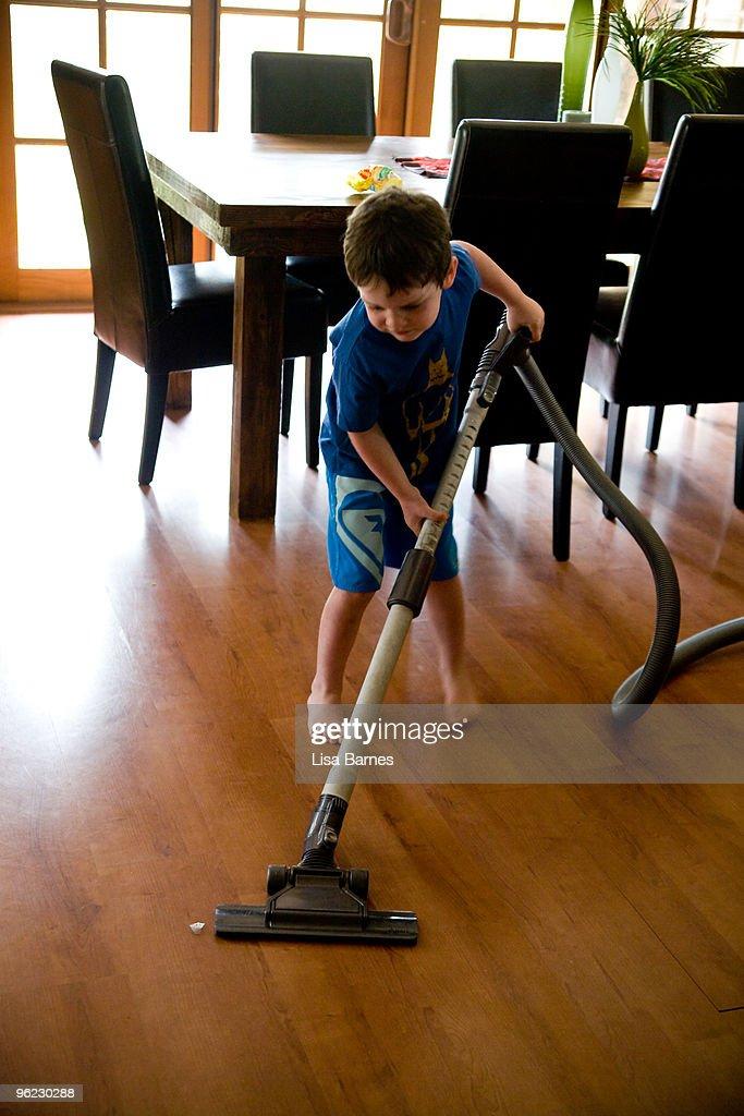 Young boy vacuuming : Bildbanksbilder
