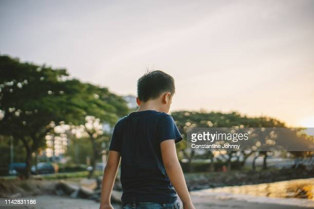 young boy view from the back - sad child stock pictures, royalty-free photos & images