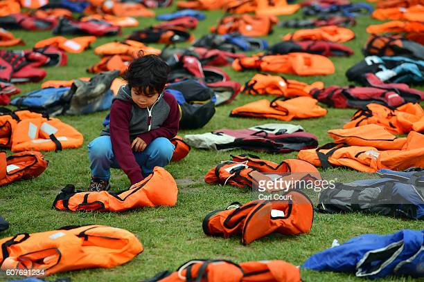 A young boy views lifejackets that have been used by refugees to cross the sea to Europe are laid out in Parliament Square on September 19 2016 in...