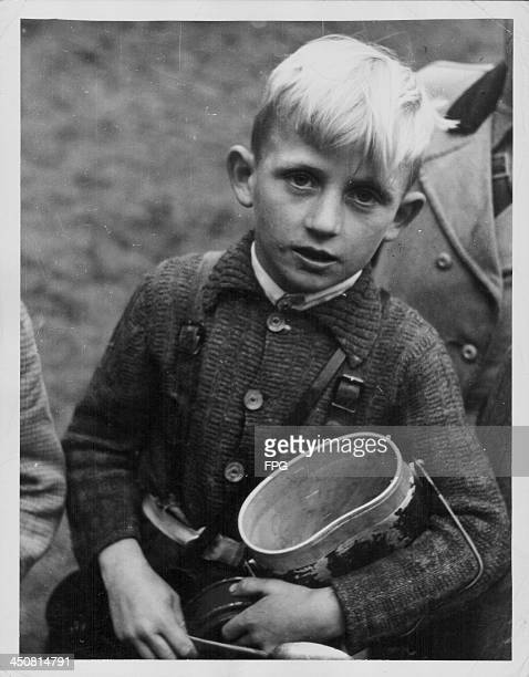 A young boy waiting to be given food handouts following the end of World War Two a time of great poverty in Germany 1947