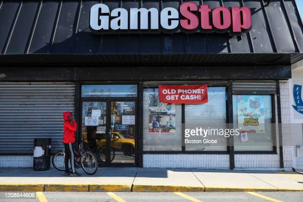 A young boy waits outside of GameStop to pick up a purchase in Roslindale MA on Friday March 27 2020 GameStop the video game retailer sent employees...