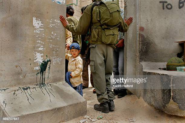 Young boy waits to be let through the small gap in the segregation wall in East Jerusalem. The segregation wall divides Israel and Palestine. East...