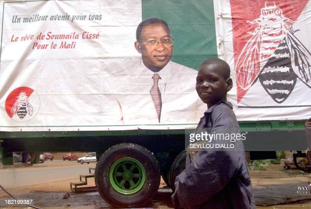 A young boy walk past a campaign banner for Soumaila Cisse presidential candidate for the party in power the Democratic Alliance 26 April 2002 in...