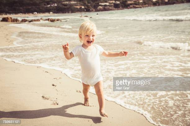Young boy walking along beach, smiling