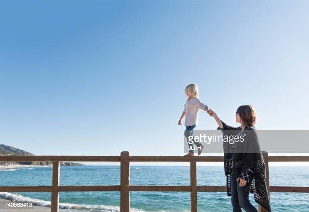 Young boy walking along fence, holding mothers hand, Laguna Beach, California, United States, North America