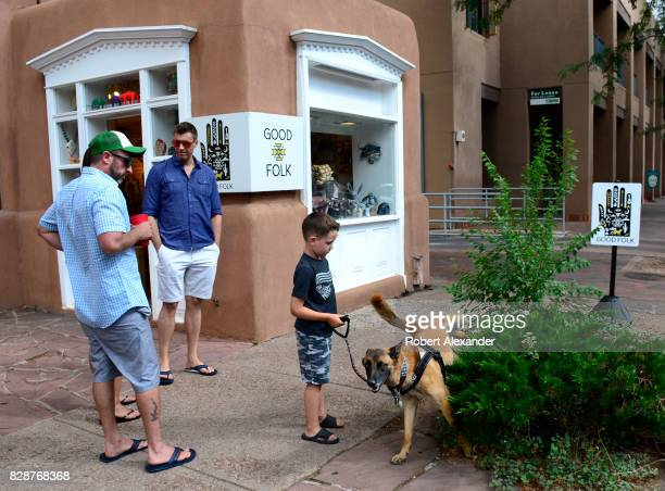A young boy walking his dog along a sidewalk in Santa Fe New Mexico pauses while the dog urinates on a bush