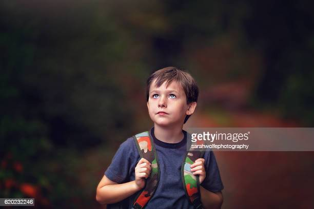 young boy walking home with backpack after school