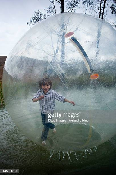 A young boy walking in an inflatable walking water ball