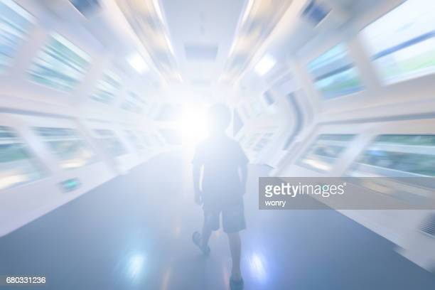 young boy walking in futuristic corridor - space station stock photos and pictures