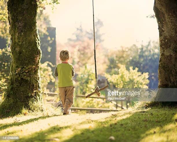 Young boy walking in garden at sunrise