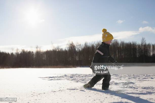 Young boy walking in snow covered landscape