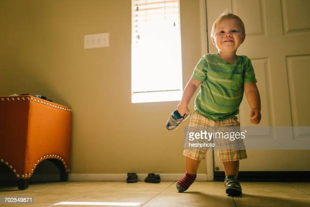 young boy walking indoors, one shoe on foot and one in hand - heshphoto stock pictures, royalty-free photos & images