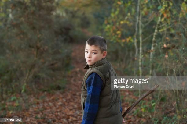 Young boy walking on a footpath through woodland