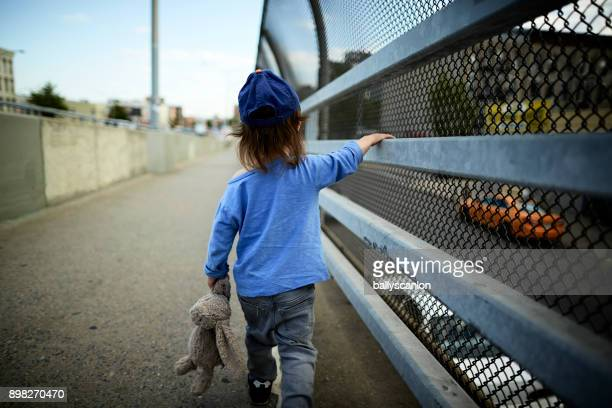 young boy walking bridge