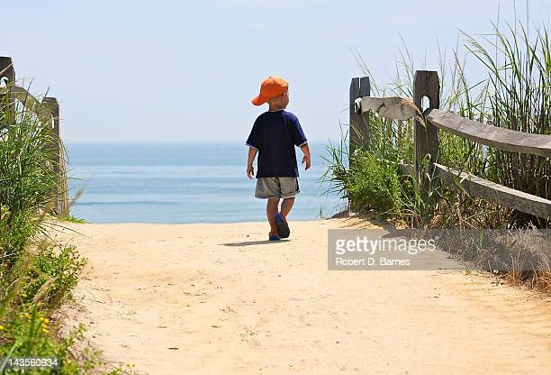 Young boy walking on sand