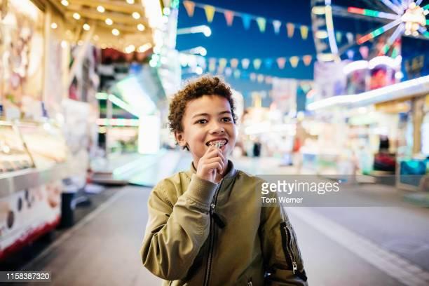 young boy walking round fun fair - round ten bildbanksfoton och bilder